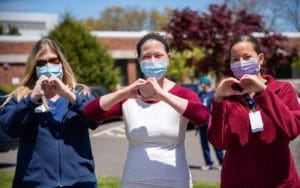 A line of nurses making a heart shape with their hands