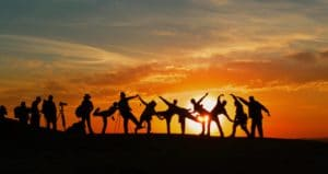 Group of people on a hill in the sunset