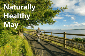 Photo of a man cycling along the Exe Estuary Trail with the text ' Naturally Healthy Month'.