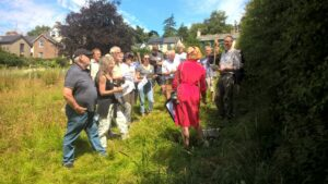 People surveying a hedge on a sunny day in Chagford